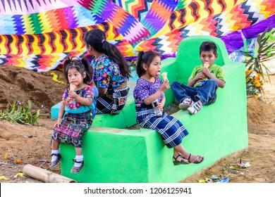 Santiago Sacatepequez, Guatemala - November 1, 2017: Indigenous Maya children eat ice cream in cemetery under giant kite during Giant kite festival on All Saints Day.