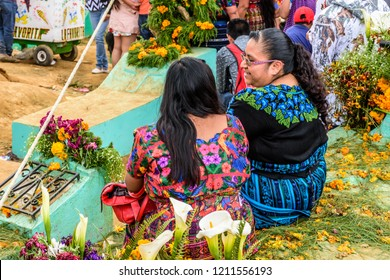 Santiago Sacatepequez, Guatemala - November 1, 2017: Indigenous Maya women sit on decorated graves at Giant kite festival honoring spirits of the dead in town cemetery on All Saints Day.