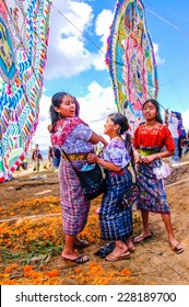 Santiago Sacatepequez, Guatemala - November 1, 2010: Mayan girls in traditional costume. Locals display huge kites (barrilete) in the cemetery on All Saints' Day to honor spirits of the dead.