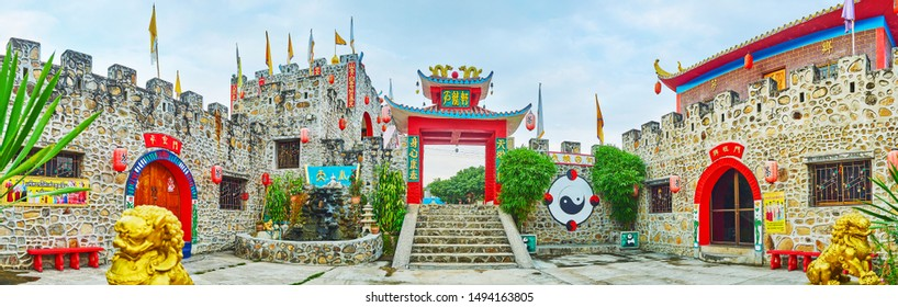 SANTICHON, THAILAND - MAY 5, 2019: Panorama of the stone castle in Chinese Yunnan village with  decorative elements - sweeping roofs, red lanterns, colored flags, foo dogs, on May 5 in Santichon