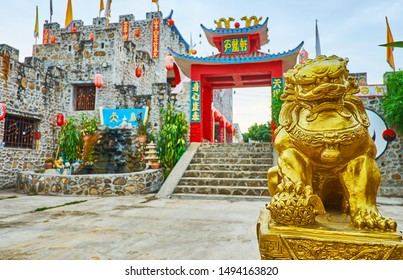 SANTICHON, THAILAND - MAY 5, 2019: Small golden foo dog (Imperial lion) guards the gate of the castle of Chinese Yunnan cultural village, on May 5 in Santichon