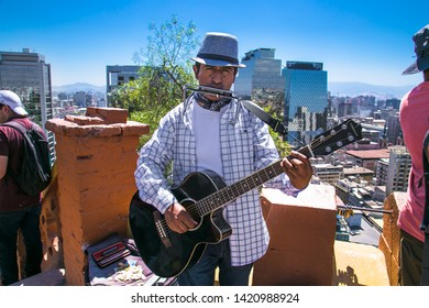 Santiego, Chile - Dec 28, 2018: Street musician paying a guitar and lip harmonique at Cerro Santa Lucia hill in Santiago ,  Chile.