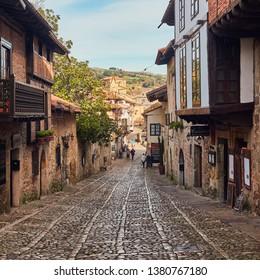 Santillana del Mar, Cantabria, Spain, December 2018. Medieval architecture of the cobbled streets and Collegiate Church of Santa Juliana of Santillana del Mar