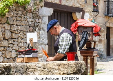 Santillana, Spain - 7th July 2018: Man with old fashioned plate camera. He takes photos of tourists.