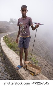 SANTO ANTAO, CAPE VERDE - AUGUST 26, 2015: Child playing with his handmade wooden truck, on the edge of a mountain road