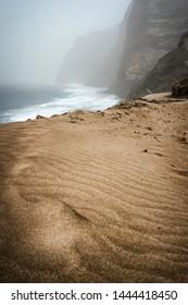 Santo Antao, Cape Verde - Cruzinha da Garca. Mountain moody coastline and Atlantic ocean waves. Sandy dune in foreground