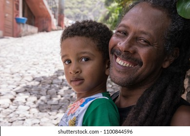 Santo Antao island, Cape Verde - august 27, 2015: Child next to his father in the street of a village in the Valley of Paul, in the north of the island