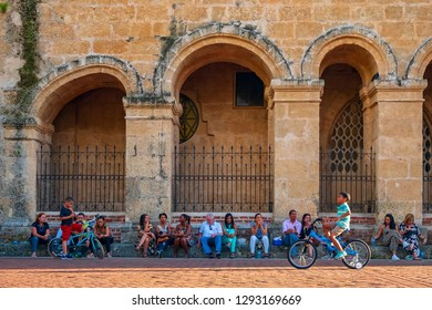 SANTO DOMINGO - DOMINICAN REPUBLIC - January 19, 2019 : People sitting in front of Cathedral Primada de America Church located in street of old town called zona colonial.