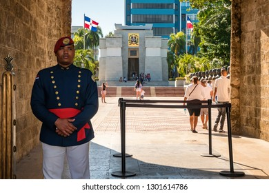 SANTO DOMINGO - DOMINICAN REPUBLIC - January 19, 2019 : Soldier on duty in entrance of Parque Independencia of Santo Domingo old town with Mausoleum and people on the background.