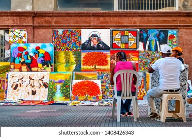 SANTO DOMINGO - DOMINICAN REPUBLIC - January 13, 2019 : Street salers of caribbean art when people pass by in old town also called zona colonial of Santo Domingo Dominican Republic.