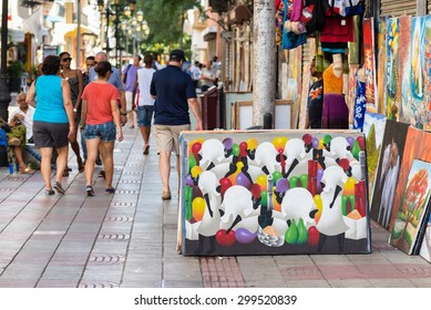 SANTO DOMINGO - DOMINICAN REPUBLIC - November 11,2014 : Street of old town called zona colonial with a haitian art picture and people pass by in Santo Domingo.