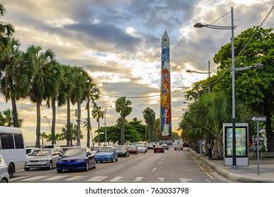 SANTO DOMINGO - DOMINICAN REPUBLIC - November 5, 2014 : El Obelisco the obelisk memorializing the Butterfly Sisters at the Malecon with traffic of cars in Santo Domingo.