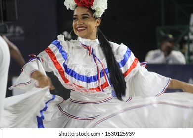 Santo Domingo, Dominican Republic - October 13 2019: Woman wearing traditional Dominican white, red, and blue costume (dress) with flowers in her hair
