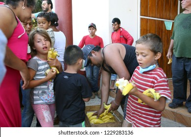 Santo Domingo Ingenio, Oaxaca/Mexico - Nov. 7, 2018: Honduran children fleeing poverty and gang violence in the second caravan to the U.S. take bananas from volunteers at an impromptu migrant shelter.
