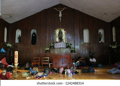 Santo Domingo Ingenio, Oaxaca/Mexico - Nov. 7, 2018:  Hondurans fleeing poverty and gang violence in the second caravan to the U.S. rest beneath the altar of a church being used as a migrant shelter.