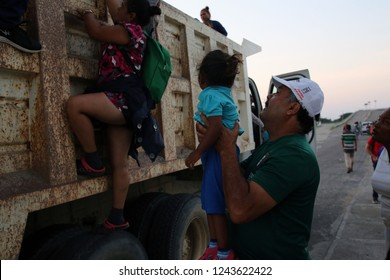 Santo Domingo Ingenio, Oaxaca/Mexico - Nov. 8, 2018:  A Honduran man fleeing poverty and gang violence in the second caravan to the U.S. lifts a child onto a truck at dawn to ride to his next stop.