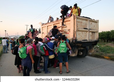 Santo Domingo Ingenio, Oaxaca/Mexico - Nov. 8, 2018: Honduran women fleeing poverty and gang violence in the second caravan to the U.S. climb onto a truck at dawn to ride to their next stop.