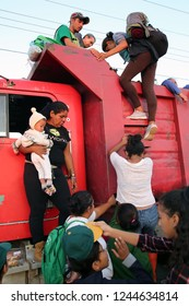 Santo Domingo Ingenio, Oaxaca/Mexico - Nov. 8, 2018: Hondurans fleeing poverty and gang violence in the second caravan to the U.S. climb onto a truck at dawn to ride to their next stop.