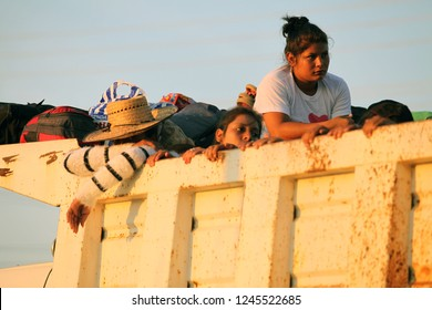 Santo Domingo Ingenio, Oaxaca/Mexico - Nov. 8, 2018: Honduran women and children fleeing poverty and gang violence in the second caravan to the U.S. look out of a dump truck going to their next stop.