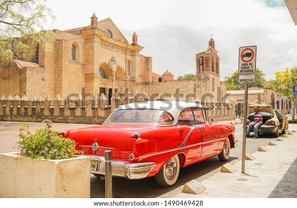 SANTO DOMINGO/DOMINICAN REPUBLIC - APRIL 20, 2019: Red classic old vintage car parked in front of Santo Domingo primate cathedral of america in a sunny day.