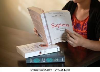 """SANTO DOMINGO/DOMINICAN REPUBLIC - AUGUST 23, 2019: Woman reads Yuval Noah Harari book """"Sapiens: A Brief History of Humankind """", Spanish edition. Best seller about human evolution and science history."""