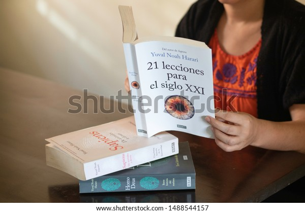 "SANTO DOMINGO/DOMINICAN REPUBLIC - AUGUST 23, 2019: Woman reads Yuval Noah Harari best seller ""21 Lessons for the 21st Century"" (Spanish Edition) on a table with other books from the same author."