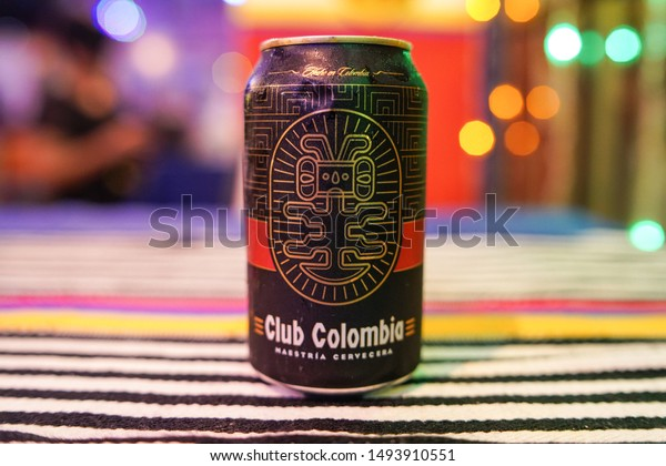SANTO DOMINGO/DOMINICAN REPUBLIC - AUGUST 30, 2019: Club Colombia premium black lager beer can over a tablecloth with Colombian flag colors and colorful bokeh background.