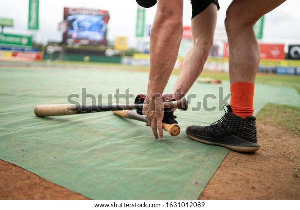 SANTO DOMINGO/DOMINICAN REPUBLIC- JANUARY 28, 2020: Baseball player picks up his glove and bats after training session in Estadio Quisqueya prior to game between Tigres del Licey and Toros del Este.