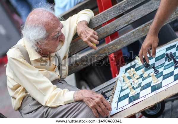 SANTO DOMINGO/DOMINICAN REPUBLIC - SEPTEMBER 18, 2010: Roque Muvdi, old tailor man with big mustache play chess in a wooden bench of Calle El Conde.