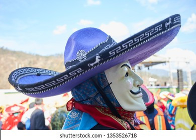 Santo Tomas Ocotepec, Oaxaca, Mexico, March 3, 2019: Side profile view of a person wearing a mask with mustache and purple charro hat during a carnival in Mexico
