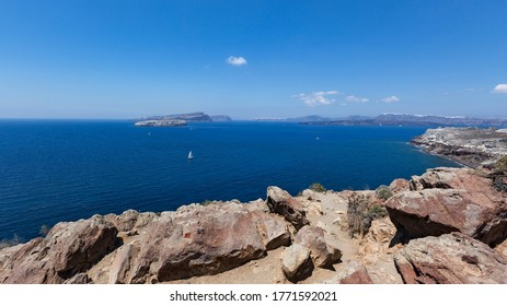 Santorini, Caldera, view from the rocky coastline of the Caldera and two volcanic islands .In the background Oia. Beautiful clear blue sky.