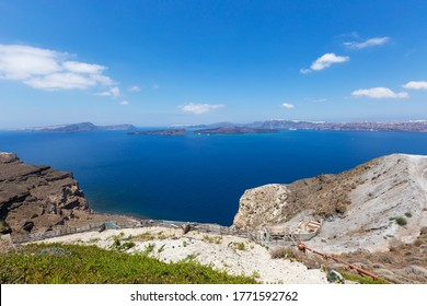 Santorini, Caldera, view from the rocky coastline of the Caldera and two volcanic islands .In the background Oia. Down on the hillside a new house. Beautiful clear blue sky.