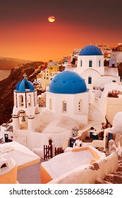 Santorini, classic view of blue dome churches at sunset. Oia Village, Greece.