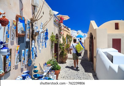 SANTORINI, GREECE - 22 JUNE 2017 : Tourists go shopping on July 28,2014 in Oia town on the Santorini island, Greece. Oia is a small town on the islands of Thira (Santorini) and Therasia, in the Cyclad
