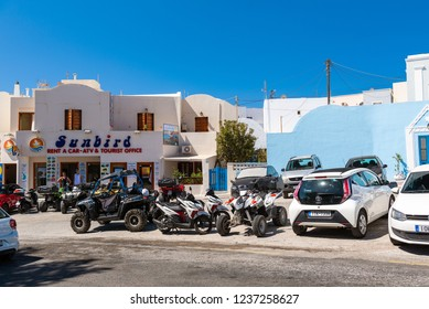 SANTORINI, GREECE - AUGUST 2018: Parked rental cars and quadricycles are staying near rental office at Imerovigli town.