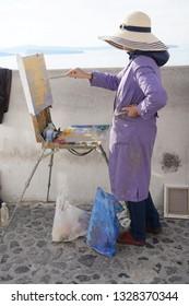 SANTORINI, GREECE - DEC 2, 2018 - Woman painting  with oils in Santorini, Greece