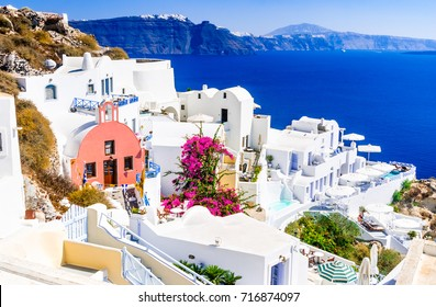 Santorini, Greece. Famous attraction of Oia village at sunset with windmill in Greek Islands, Aegean Sea.