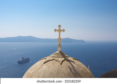 SANTORINI, GREECE, JULY 20: Details of Orthodox church and religious cross with the Aegean Sea in the background with cruising passengers boats and blue sky. Greece 2013