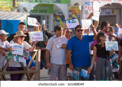 SANTORINI, GREECE, JULY 20: Unidentified group of guides trying to attract tourists to their pensions and hotels at their arrival at the harbor of Santorini island, Greece 2013.
