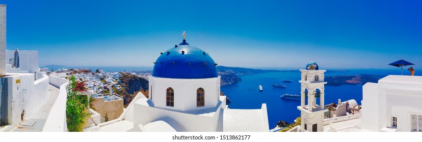 Santorini, Greece - July 30 2019 Panoramic view of Nikolaus monastery with domed cathedral and bell tower on seashore under blue sky in Santorini Greece