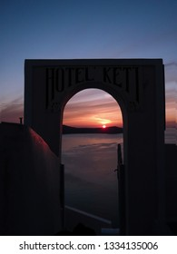 Santorini, Greece - May 02, 2009: Sunset through the stone gate of Hotel Keti at the Santorini Island, Greece. Santorini is a popular tourist destination and the sunset is one of the attractions.
