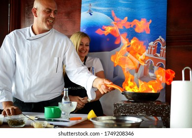 SANTORINI, GREECE - MAY 18: The cooking of traditional Greek dishes by chef with help of tourist is in Greek restaurant on May 18, 2014 in Santorini, Greece.