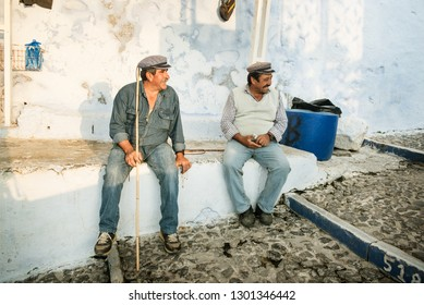 Santorini, Greece - October 19, 2018: two men sheperds who conduct donkeys with tourists in Fira, Santorini, are having a rest, smiling and happy after a hard day, in their dirty worn out clothes