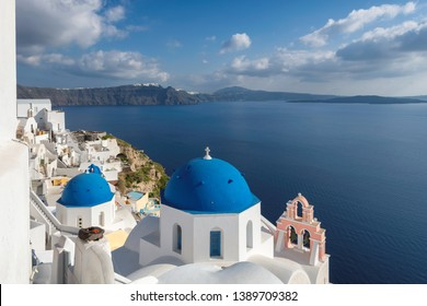 Santorini, Greece. Romantic view of Greek orthodox church with blue domes and sea in Oia town, Santorini island, Greece.