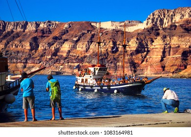 SANTORINI, GREECE - SEP 04: Cruise ship with tourists arrives to harbor and people watching it from the pier on September 03, 2017 in Athinios port, Santorini island, Cyclades, Aegean Sea, Greece