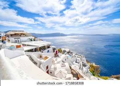 Santorini, Greece - September 13 2019: The whitewashed hillside town of Oia, Greece on Santorini Island, filled with cafes and hotels overlooking the Aegean Sea and volcanic Caldera.