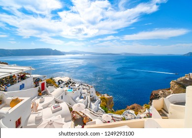 Santorini, Greece - September 18 2018: View of the Aegean Sea as a boat crosses the water inside the caldera from a cliffside overlook in Oia, Greece.