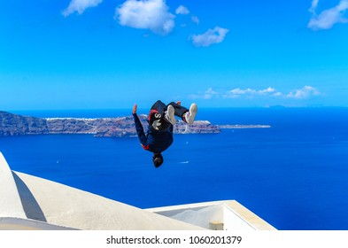SANTORINI, GREECE - SEPTEMBER 2013: Young man doing Parkour and Free running. Professional athlete performing a backflip on a roof in Santorini, Island, Greece, Europe.