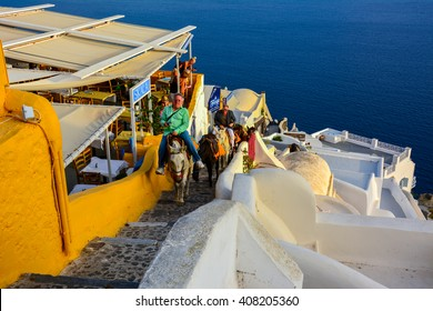 SANTORINI, GREECE - SEPTEMBER 22, 2014 - tourists who climb from the port on the back of donkeys in Santorini