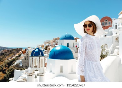 Santorini. Holidays. Young woman in summer dress, glasses and hat is enjoying the sunny weather outside